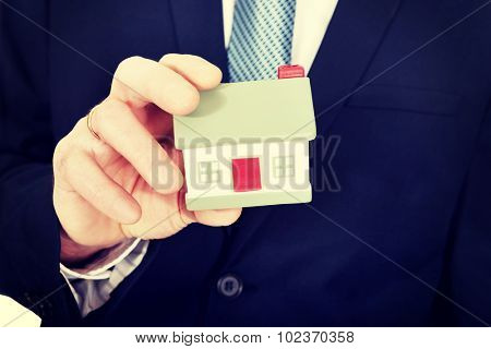 Close up on businessman hand holding house model.