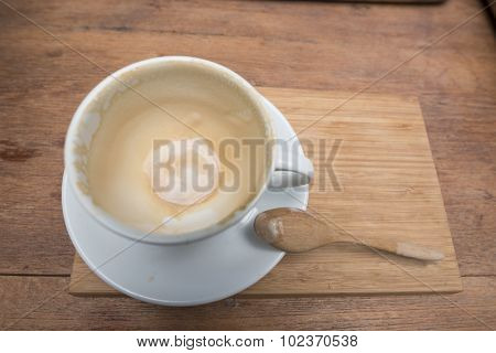 Empty coffee cup after drink with spoon on wood table.