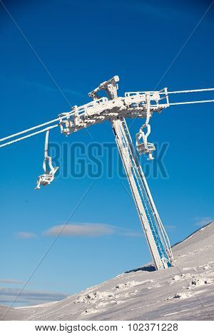 Frozen Chair Lift At Snow Resort In Winter Mountains On Sunny Day