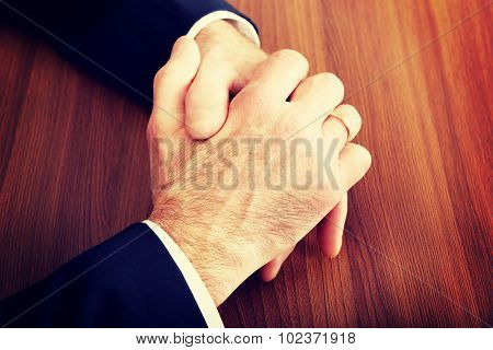 Close up of businessman clenched hands on the desk.
