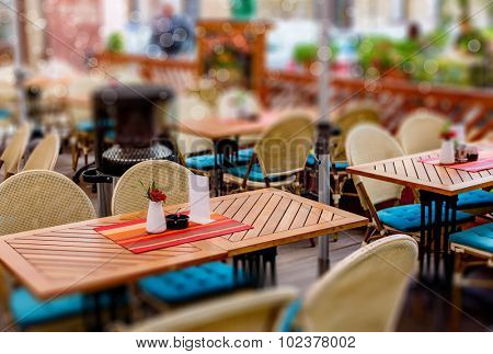 treet view of a Cafe terrace with tables and chairs in european city