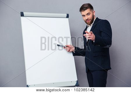 Portrait of a confident businessman presenting something on blank board over gray background
