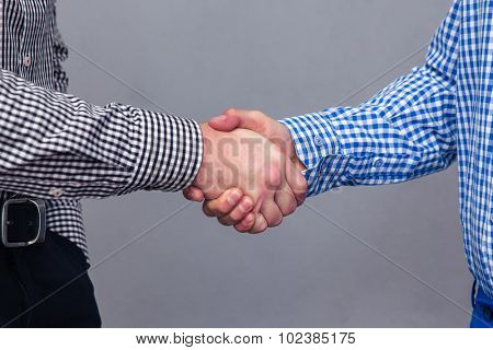 Portrait of a two male hands doing handshake over gray background