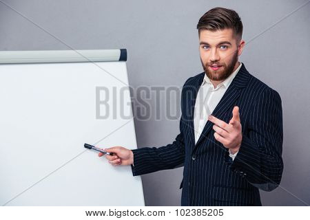 Portrait of a young businessman in suit presenting something on blank board over gray background