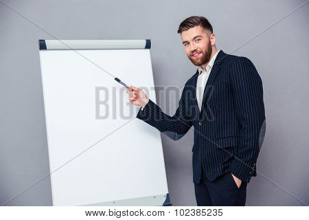 Portrait of a happy businessman presenting something on blank board over gray background