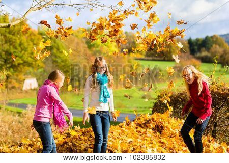 Girls having fun throwing fall or autumn leaves in park