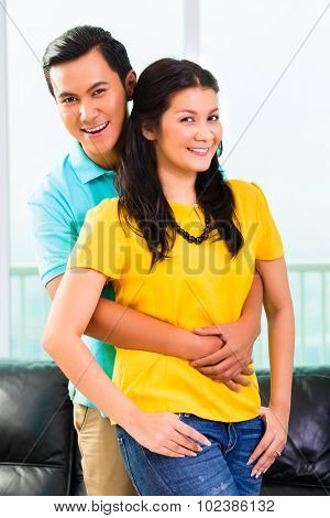 Young Asian handsome couple in apartment having long-term relationship cuddling together