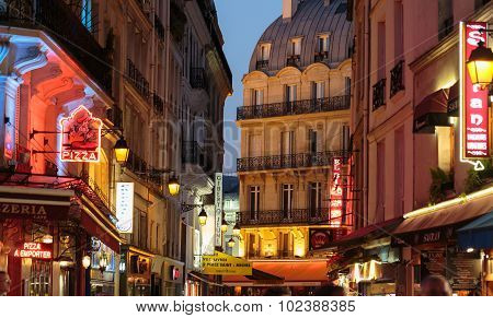 PARIS, FRANCE - SEPTEMBER 11, 2014: Latin Quarter of Paris France. Narrow street of Paris among old traditional parisian houses and cafe in Paris.
