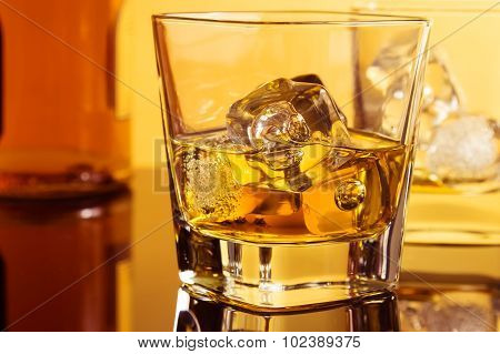 Close-up Of Two Glasses Of Whiskey Near Bottle On Table With Reflection, Warm Atmosphere