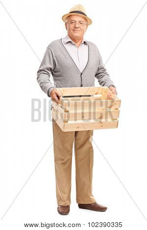 Full length portrait of a senior gentleman holding an empty wooden crate and looking at the camera isolated on white background