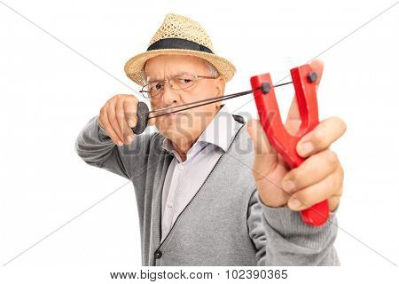 Angry senior gentleman aiming to shoot a rock with a slingshot isolated on white background