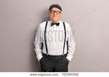 Joyful senior in artistic clothes posing in front of a gray wall and looking at the camera