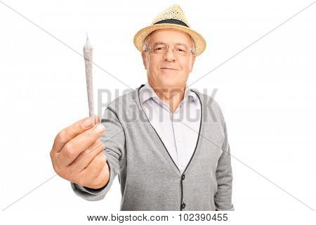 Cheerful mature man handing medicinal marijuana towards the camera isolated on white background