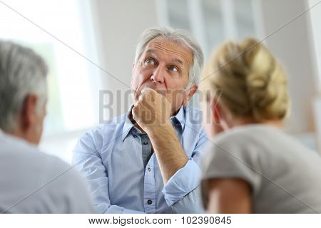 Senior man attending meeting with group therapist