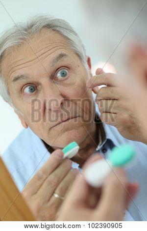 Closeup of senior man putting contact lens