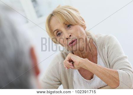 Portrait of elderly woman talking to husband