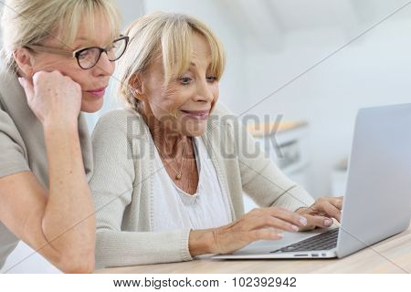 Senior women websurfing with laptop computer