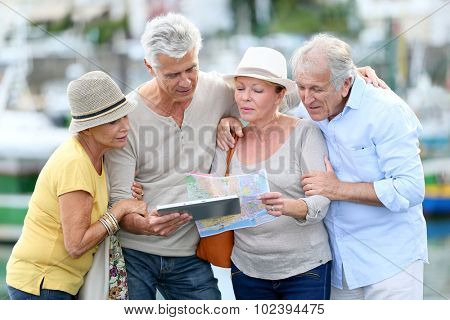 Senior tourists using tablet on visiting journey