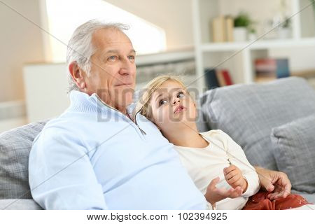 Portrait of grandfather with little girl sitting in couch