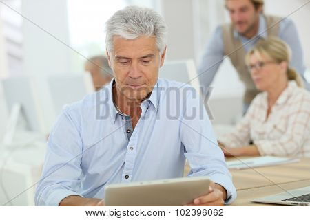 Portrait of senior man working on tablet, training class