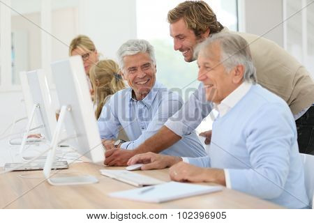 Instructor helping senior men with computing class