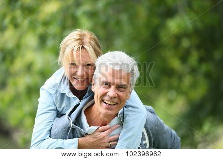 Senior man giving piggyback ride to his wife