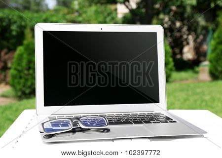 Laptop and glasses on wooden table outdoor