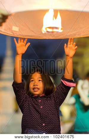 CHIANG MAI, THAILAND, JANUARY 1, 2015 :  A little girl is sending a floating traditional fire lantern to the sky and making a wish for the new year in Chiang Mai, Thailand