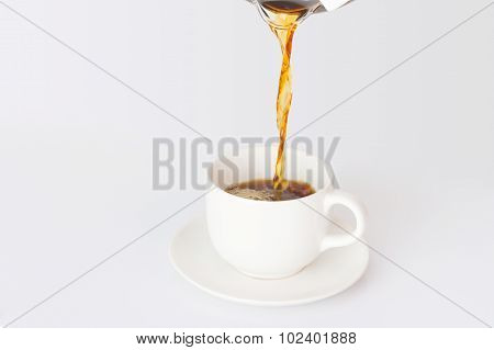 Black Coffee Being Poured Into A White Coffee Cup