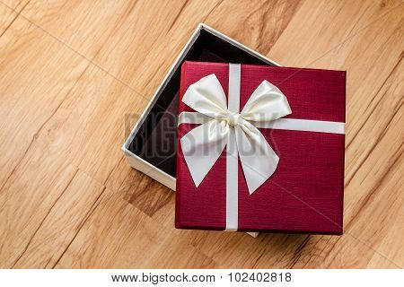 Empty open gift box on wood