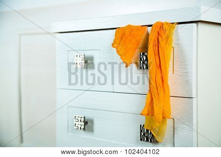 White wooden chest of drawer with scarf in opened drawer
