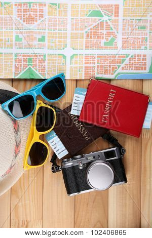 Sunglasses, passport and map, close up, on wooden background. Preparing for travel concept