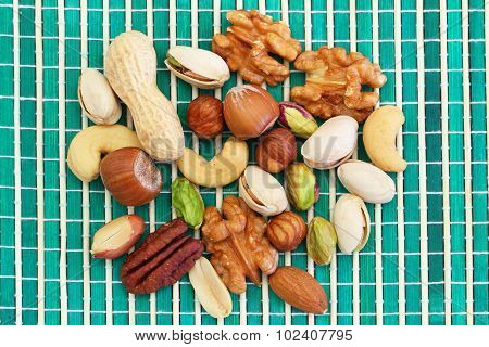 Selection of nuts, almonds and sultanas on green bamboo mat