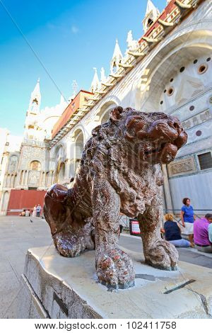 VENICE, ITALY - SEPTEMBER 2014 : People walking around near the iconic Red marble statue of lion at St Mark's Square in Venice, Italy on September 15, 2014. Lion is the symbol of Venice, Italy.