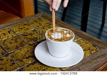 A Coffee Cup Latte Being Stirred By Cinnamon Sticks.