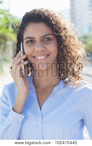 Laughing Latin Woman With Blue Blouse At Phone In The City
