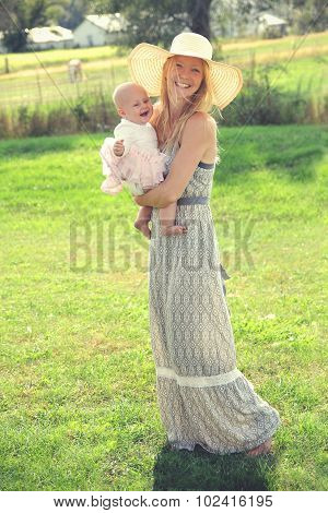 Happy Young Mother And Baby In Country