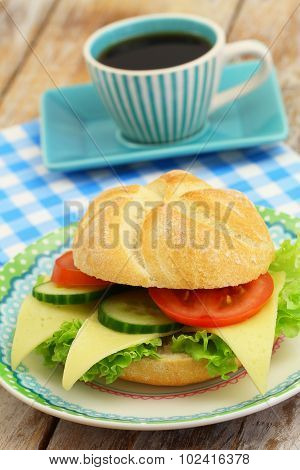 Cheese roll with lettuce, tomato and cucumber and cup of coffee