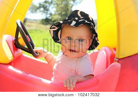 Beautiful Baby Playing Outside In Toy Car