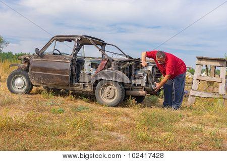 Senior man repairing self-made car