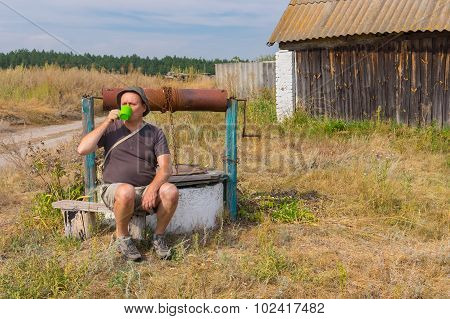 Tired traveller drinking water at country draw-well