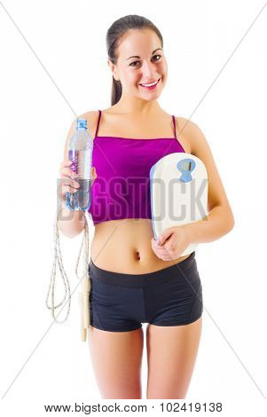 Young sporty girl with skipping rope and scales isolated