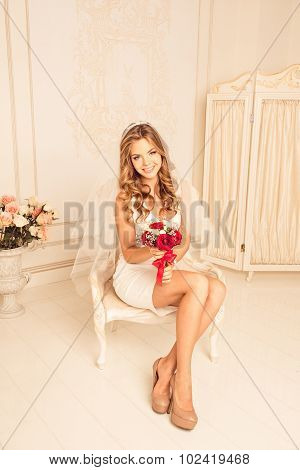 Bride In Bedroom Sitting On A Chair With Wedding Bouquet