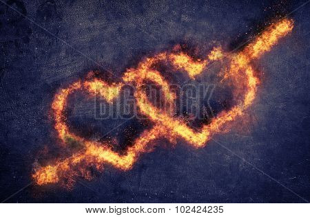 Pair of flaming overlapping Valentines hearts pierced by Cupids arrow of Love over a dark textured background with copyspace for your romantic message