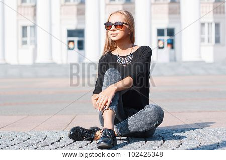 Beautiful Stylish Girl In A Black T-shirt, Jeans And Shoes Sitting On The Tile