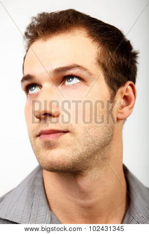 Face of serious man looking up over white