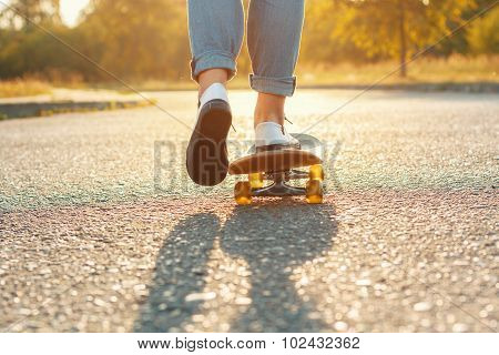 Skateboarding Legs At Skate Park. Beautiful Weather With The Sunset. Woman Moves Forward