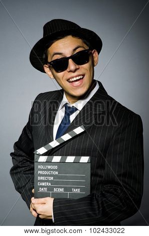 Young man in elegant suit holding clapperboard against gray