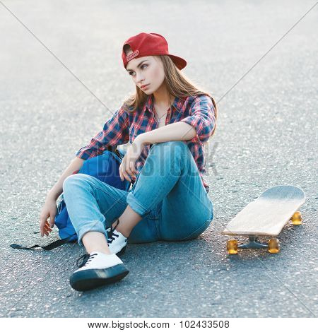 Portrait Of A Beautiful Woman In A Shirt And A Baseball Cap With A Skateboard In The Park.