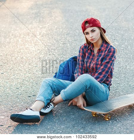 Beautiful Young Girl Sitting On The Asphalt With A Skateboard. Outdoor Lifestyle Picture On A Sunny